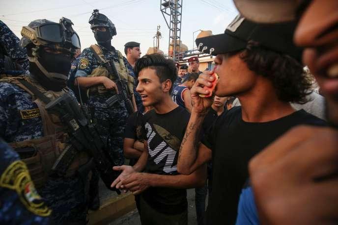 Des manifestants s'entretiennent avec des membres de la police à Sadr City (Irak), une ville à majorité chiite, le 7 octobre 2019.