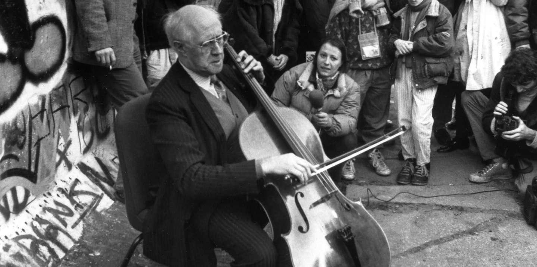 Berlin, novembre 1989 (après l'ouverture des postes-frontières de la RDA, 9.11.1989).  Le violoncelliste russe Mstislav Rostropovitch jouant un morceau de Bach devant le Mur non loin de Checkpoint Charlie (au fond, l'immeuble d'Axel Springer).  11 novembre 1989 (Succo).