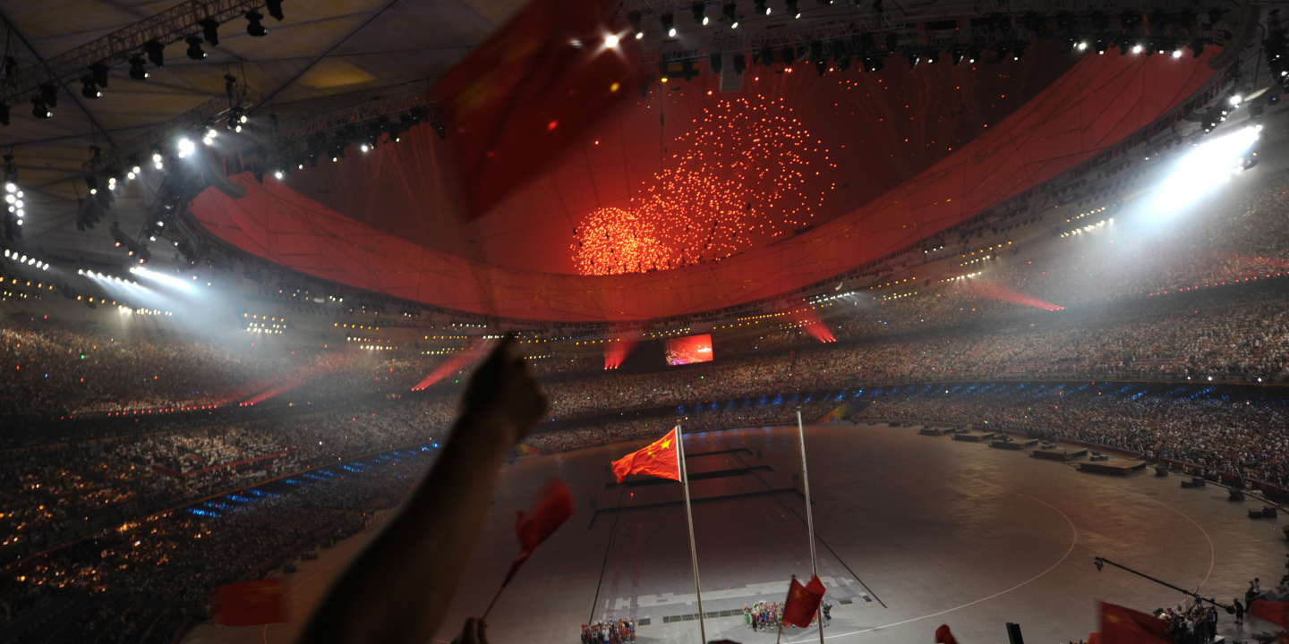 General view shows children from 56 Chinese ethnic groups sing the national anthem as fireworks light up the sky during the opening ceremony of the 2008 Beijing Olympic Games in Beijing on August 8, 2008. The three-hour show at Beijing's iconic