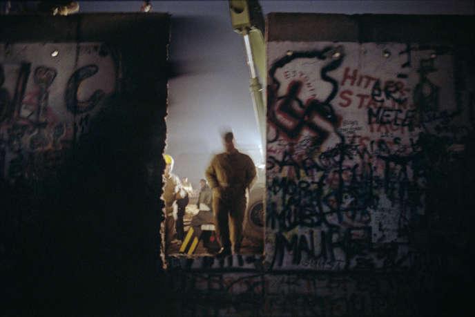 Việc tháo dỡ Bức tường Berlin, nhìn từ phía tây, gần Cổng Brandenburg, vào đêm ngày 9 tháng 11 năm 1989.