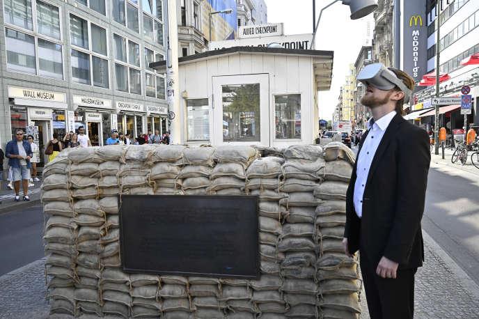 Jonas Rothe, le fondateur de TimeRide, pose avec un casque de réalité virtuelle devant Checkpoint Charlie, le 22 août. Grâce à cette technologie, sa société propose aux touristes des visites virtuelles du Berlin des années 1980 à bord d'un bus.