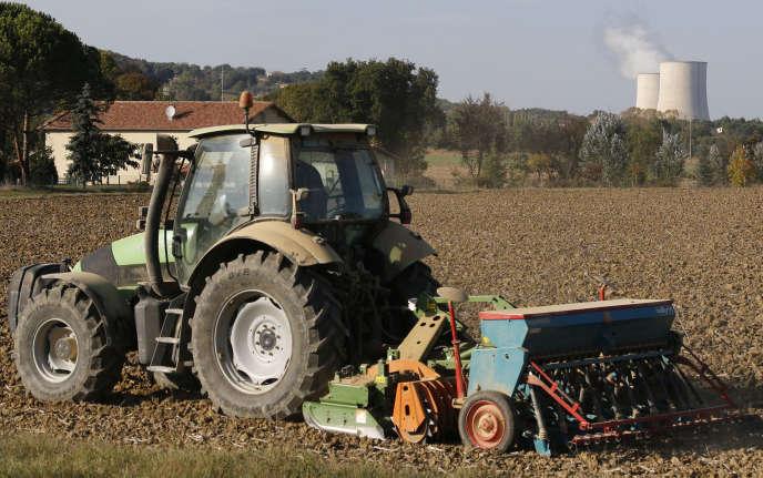 Un agriculteur cultive son champ à proximité des tours de refroidissement de la centrale nucléaire de Golftech (Tarn-et-Garonne), en octobre 2014.