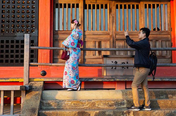 Un touriste photographie son amie habillée en kimono au temple Kiyomizu-dara, le 31octobre à Kyoto.