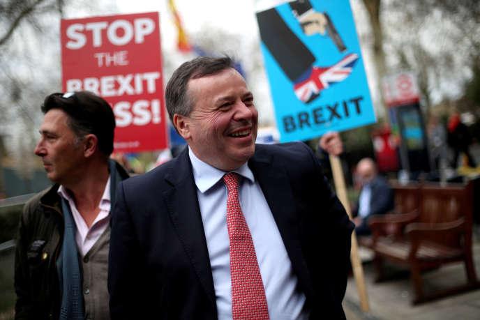 Arron Banks passe devant des manifestants pro-Brexit à l'entrée du Parlement britannique, en mars 2019.