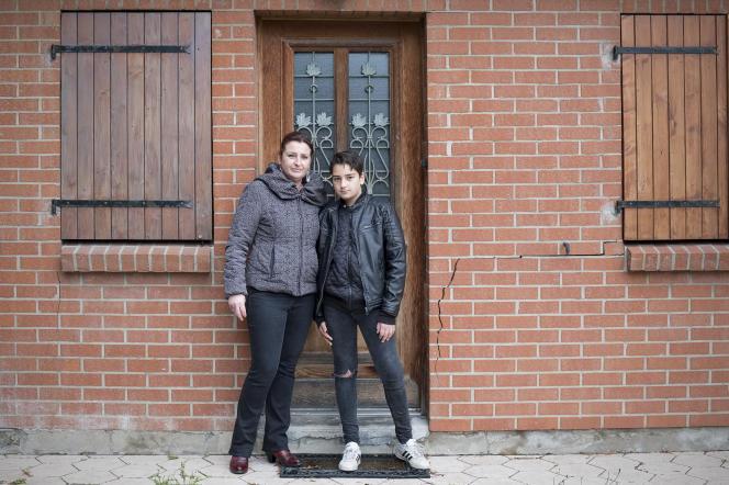 Dorine et Sasha devant la porte d'entrée qui ne s'ouvre plus depuis deux ans à cause des mouvements du terrain.