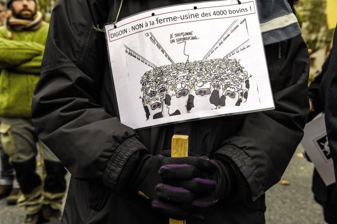 Un membre de la «Confédération paysanne» porte une pancarte contre le projet d'une ferme-usine de plus de 4000 animaux.