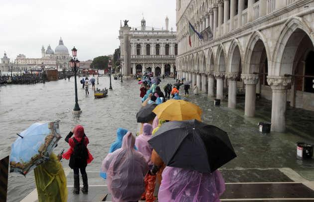 Des personnes marchent sur un podium aménagé à l'occasion de la «marée haute» survenue à Venise, en Italie, le 12 novembre.