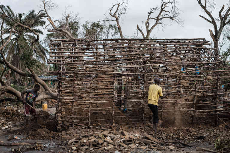Men remove the remaining of mudwall as they repair their house which was destroyed by the winds of cyclone Idai in Beira, Mozambique, on March 27, 2019. - Five cases of cholera have been confirmed in Mozambique following the cyclone that ravaged the country killing at least 468 people, a government health official said on March 27, 2019. Cyclone Idai smashed into Mozambique on March 15, unleashing hurricane-force winds and heavy rains that flooded much of the centre of the poor southern African country and then battered eastern Zimbabwe and Malawi. (Photo by Yasuyoshi CHIBA / AFP)