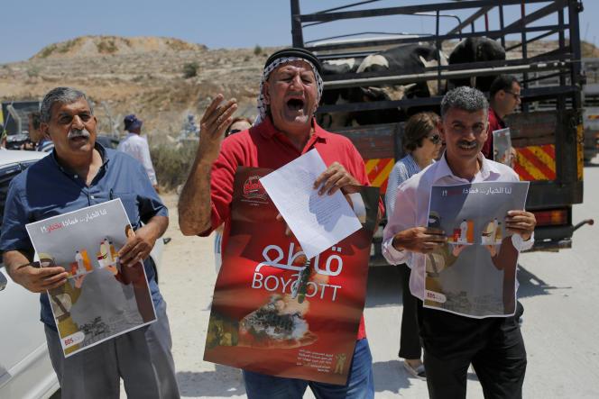 Des Palestiniens appellent au boycottage des produits israéliens originaires des colonies, au point de contrôle d'Ofer, près de Ramallah, le 6 août.