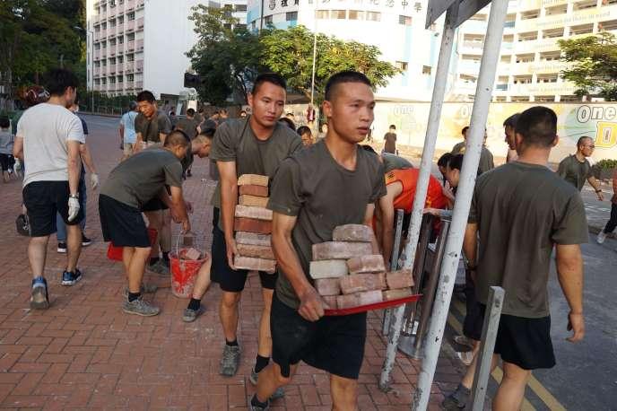 Des membres de l'armée chinoise participent au nettoyage des rues de Hongkong, samedi 16 novembre.