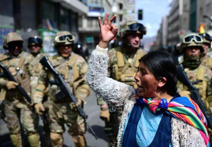 Une partisane d'Evo Morales devant des militaires déployés à La Paz, la capitale du pays, le 15 novembre.