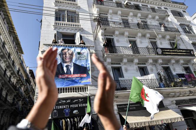 Des partisans d'Abdelkader Bengrina devant une affiche du candidat à la présidentielle, en Algérie, le 17novembre 2019.