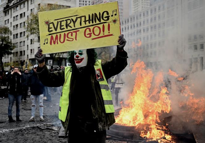 Un manifestant grimé en Joker tient une banderole sur la place d'Italie, à Paris, le 16novembre 2019, lors d'une manifestation marquant le premier anniversaire des«gilets jaunes».