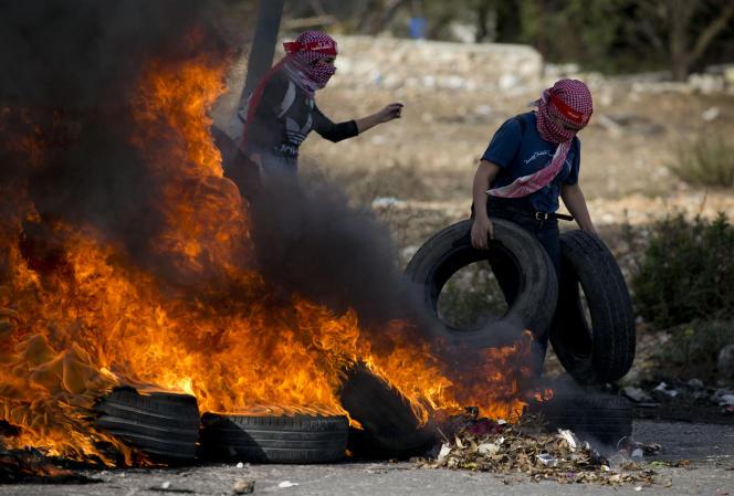 Des Palestiniens brûlent des pneus pour répondre à l'offensive israélienne contre Gaza, à Ramallah, le 16 novembre.