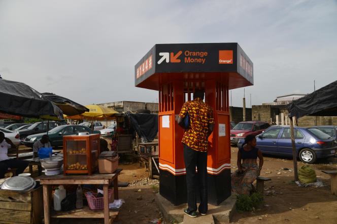 Un homme retire de l'argent à un guichet Orange Money, en mai 2015, à Abidjan (Côte d'Ivoire).