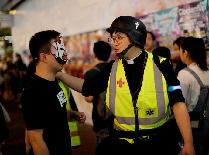 Un pasteur discute avec un manifestant lors d'une marche antigouvernement le 31octobre à Hongkong.