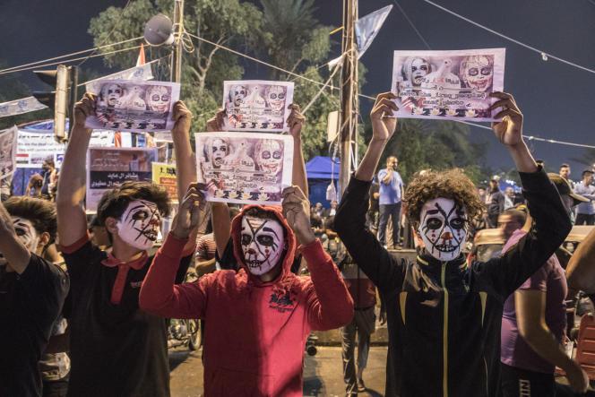 Des jeunes manifestants irakiens grimés brandissent des pancartes sur la place Tahrir, à Bagdad, le 15 novembre. L'unde leurs slogans est : «Le gouvernement nous voit comme le diable alors que nous sommes pacifiques.»