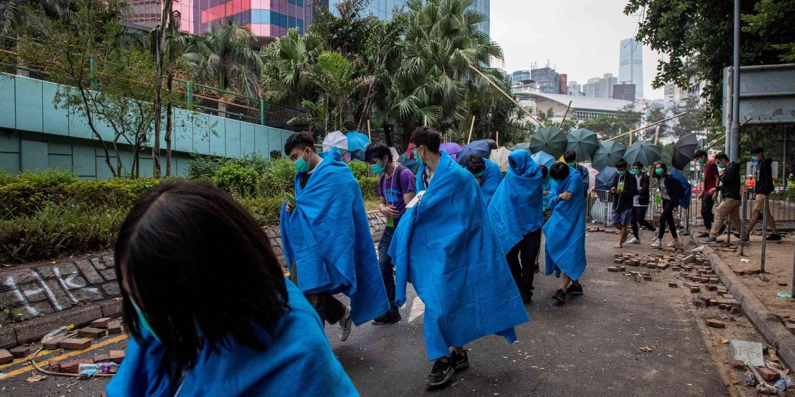 Exténués, des manifestants prodémocratie quitte le campus de l'Université polytechnique de Hongkong, le 19 novembre 2019.
