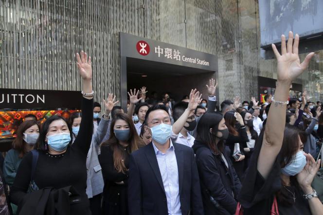 Des manifestants prodémocratie font le signe de leurs « cinq demandes», dans le quartier des affaires, mercredi 20 novembre.