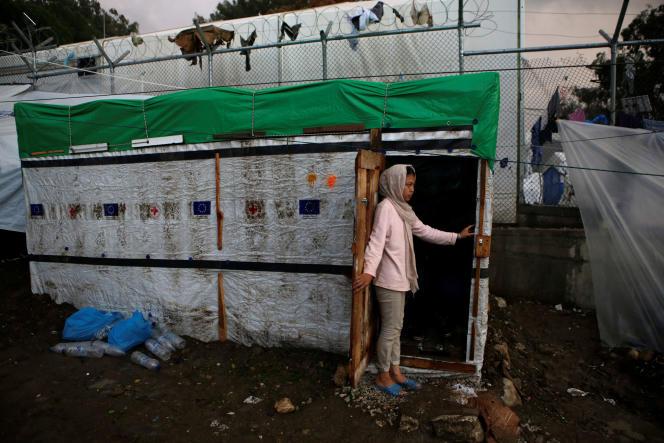 Une jeune fille se tient à l'entrée d'un abri de fortune dans un camp de réfugiés et de migrants à Moria, sur l'île de Lesbos, le 22 novembre.