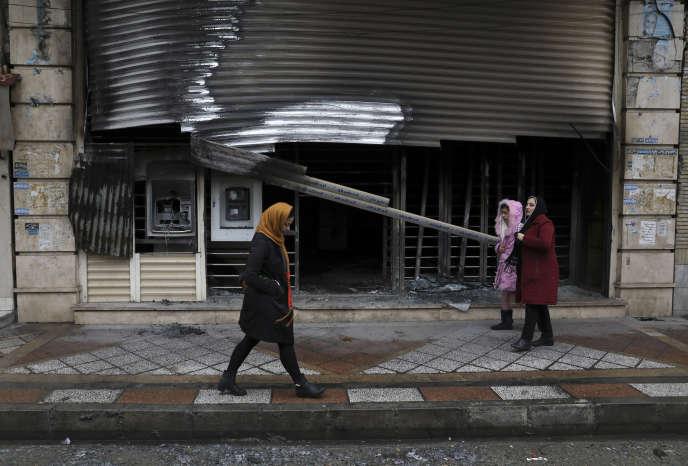 Des piétons passent devant une banque incendiée lors des manifestations à Téhéran, le 20 novembre.