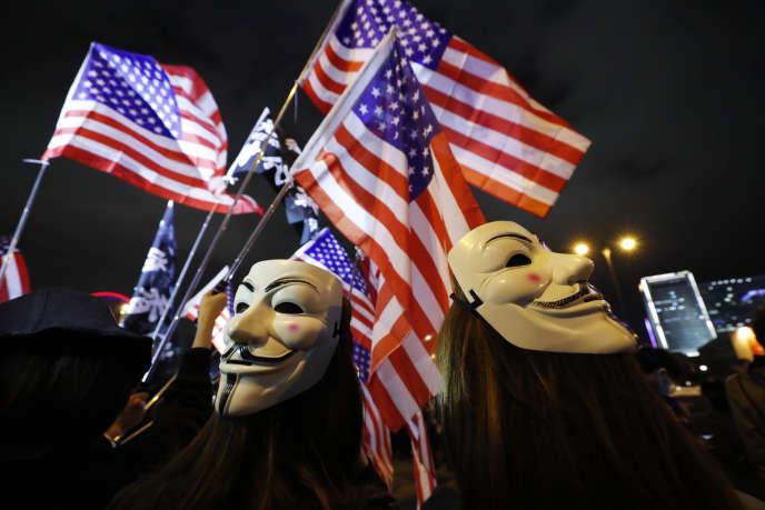 Des manifestants hongkongais brandissent des drapeaux américains après la loi prodémocratie promulguée par Donald Trump, le 27 novembre.