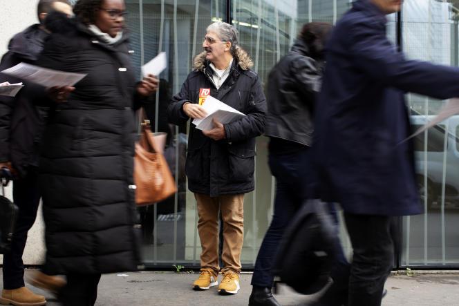 Edouard Zenou, retraité cheminot, distribue des tracts à la sortie du RER sur l'esplanade Henri-de-France à Paris, le 28 novembre.