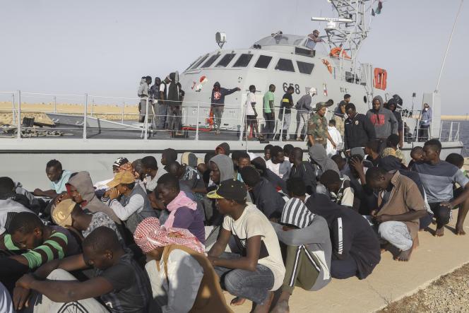 Des migrants secourus attendent devant un bateau des gardes-côtes dans la ville de Khoms, dans le nord-ouest de la Libye, le 1er octobre 2019.