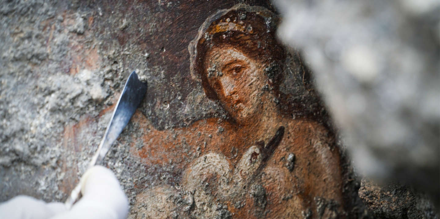 This photo taken on November 19, 2018 and handout on November 21 by the Press Office of the Pompeii Archaeological Park shows an archaeologist clearing a newly-discovered fresco, representing Greek mythological princess Leda and a swan, in an ancient Pompeii bedroom. - The fresco represents a sensual Greek mythological princess Leda and a swan on her lap, directly looking at whoever watches it. The fresco was discovered on November 16, 2018 during ongoing work to consolidate the ancient city's structures. The ancient Roman city of Pompeii, now near modern Naples, was destroyed in the eruption of Mount Vesuvius in AD 79. (Photo by Cesare ABBATE / PRESS OFFICE OF THE POMPEII ARCHAEOLOGICAL PARK / AFP) / RESTRICTED TO EDITORIAL USE - MANDATORY CREDIT