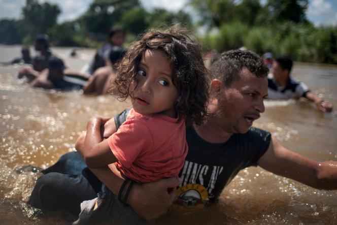 En octobre 2018, un homme porte un enfant de 5 ans pour traverser le fleuve Suchiate, à la frontière entre le Mexique et le Guatemala.