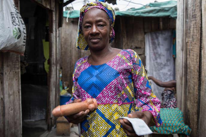 Amy Touré, «paire éducatrice», sensibilise les travailleuses du sexe aux risques du VIH dans les quartiers de prostitution d'Abidjan, en Côte d'Ivoire, en leur montrant comment mettre en place un préservatif.