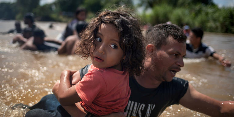 Luis Acosta holds 5-year-old Angel Jesus, both from Honduras, as a caravan of migrants from Central America en route to the United States crossed through the Suchiate River into Mexico from Guatemala in Ciudad Hidalgo, Mexico, October 29, 2018. Picture taken October 29, 2018. REUTERS/Adrees Latif/File Photo   SEARCH