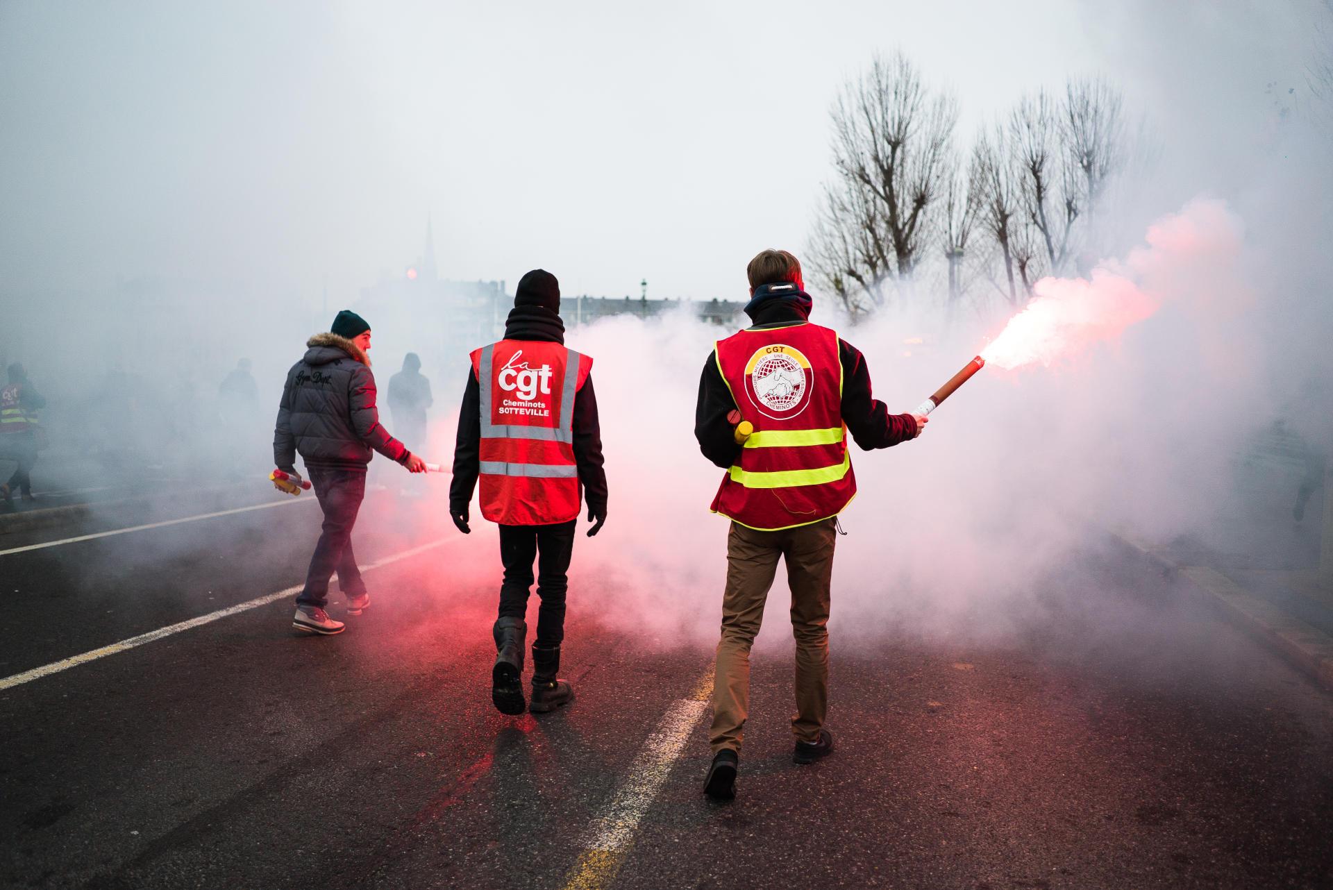 Trois cheminots en grève défilent sur le pont Corneille à Rouen lors de la manifestation du 5 décembre 2019.