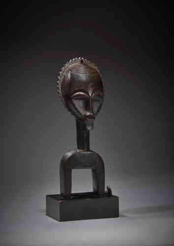 «Helena Rubinstein forgea sans doute son goût pour la sculpture africaine à travers des séries de petits objets figuratifs qui répondaient à son intérêt grandissant pour les formes classiques de la statuaire africaine, notamment celles de la Côte d'Ivoire. Cet étrier de poulie de métier à tisser, véritable chef-d'œuvre de l'art baoulé, dont le visage renvoie au masque-lune, transcende la dimension fonctionnelle et se démarque parmi d'autres exemplaires de plus petite taille. Présenté soit seul, soit entouré d'autres étriers de poulie selon un principe de taille décroissante, il fut, par son mode d'exposition, identifié comme une pièce exceptionnelle.»