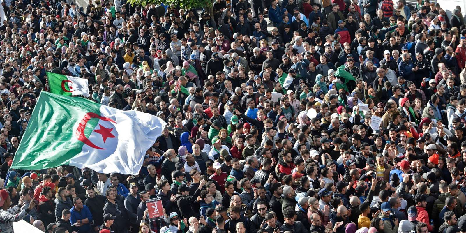 TOPSHOT - Algerian protesters take part in an anti-government demonstration in the capital Algiers on December 12, 2019 during the presidential election. Five candidates are running in Algeria's presidential election to replace ousted Algerian president Abdelaziz Bouteflika, the country's election authority said Saturday, amid widespread protests against the vote. Former premiers Ali Benflis and Abdelmadjid Tebboune are considered front-runners in an election opposed by the mass protest movement that alongside the army forced Bouteflika to resign in April after 20 years in power. No opinion polls have been published but observers expect an extremely low turnout nationwide after months of demonstrations opposing the vote. / AFP / RYAD KRAMDI