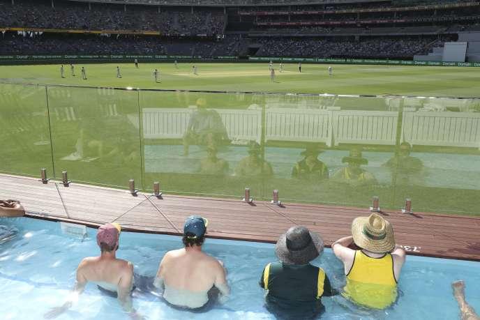 Des spectateurs regardent un match de cricket (Australie-Nouvelle-Zélande) depuis une piscine dans un stade de Perth, sur la côte ouest de l'Australie, le 12 décembre.