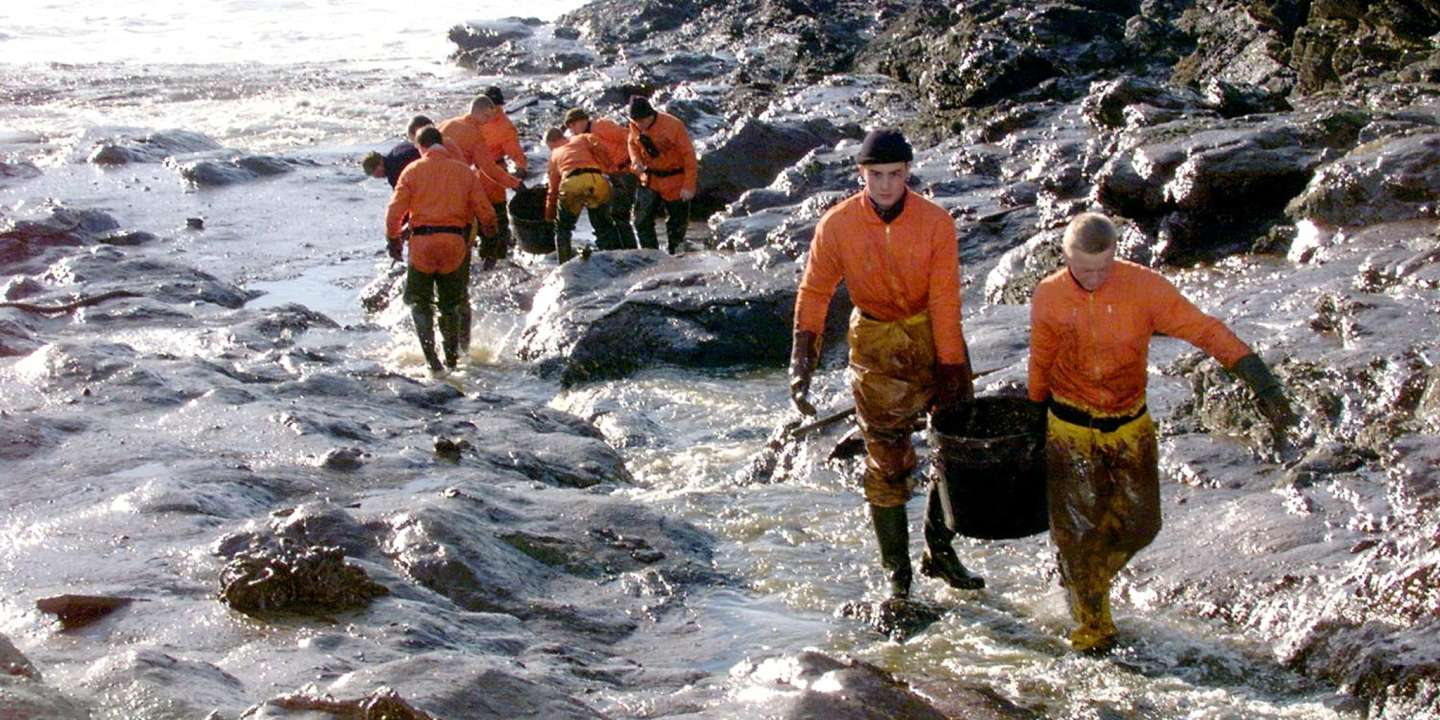 (FILES) In this file photo taken on December 29, 1999, French Civil Security soldiers carry garbage cans filled with oil they recovered on rocks on the western French island of Belle-Ile, following the sinking of the Maltese-registered tanker Erika off the coast of Brittany. The Erika tanker split in half and sank south of Brittany's Finistere department on December 11, 1999, while carrying 30,000 tons of heavy fuel, causing one of the worst oil spills in France, affecting 400 km of coastline from the tip of Brittany to the Ile de Re.    / AFP / MARCEL MOCHET