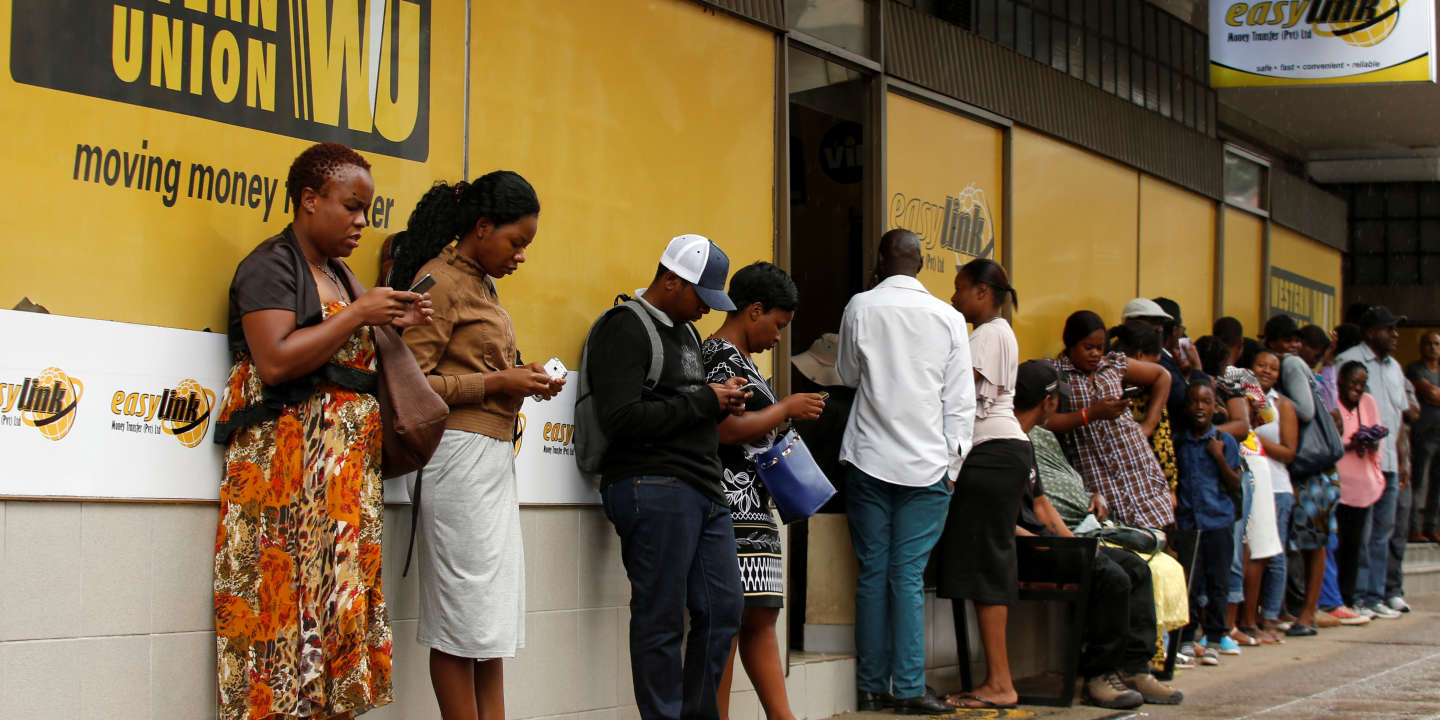 Zimbabweans queue outside a Western Union branch in Harare, Zimbabwe, February 26, 2019. REUTERS/Philimon Bulawayo - RC16ACF17C00