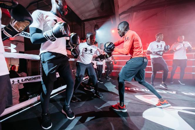 Dans une ambiance tamisée par les projecteurs orangés, les jeunes licenciés en boxe écoutent les consignes et bénéficient des conseils deSouleymane Cissokho.