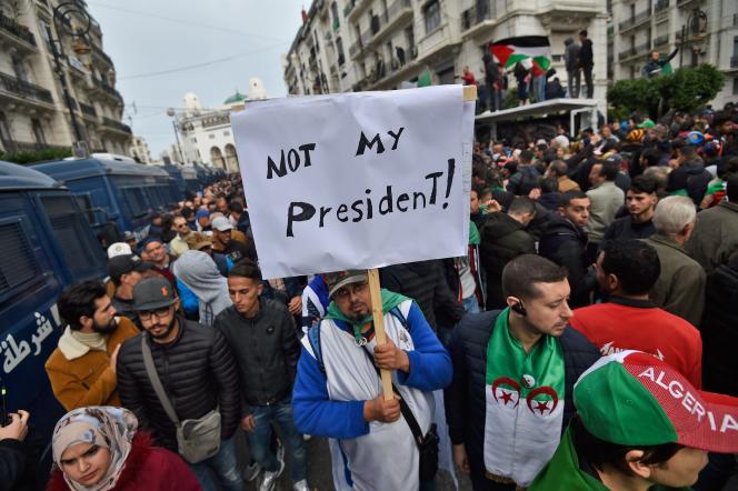 Un manifestant tient une pancarte à Alger, vendredi 13 décembre.