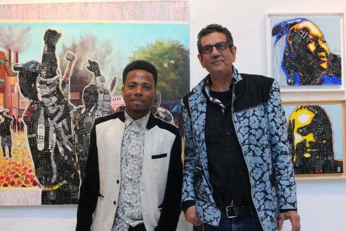 L'artiste ivoirienMounou Désiré Koffi (à gauche) devant l'une de ses œuvres, « La Révolte» (2018), en compagnie d'Olivier Sultan à la galerie Art-Z, en novembre 2019.