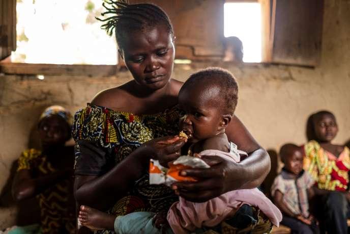 Une femme nourrit son enfant avecdes alimentsthérapeutiquesprêtsàl'usage en 2016 en République démocratique du Congo.