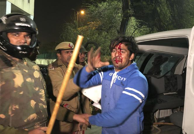 La police arrête un étudiant devant l'université musulmane Jamia Millia le 15 décembre à Delhi.