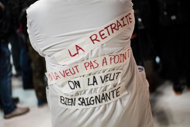Des figures de la gauche viennent saluer les grévistes de la Gare de Lyon, à Paris. Sur sa blouse, dans son dos, une soignante a inscrit