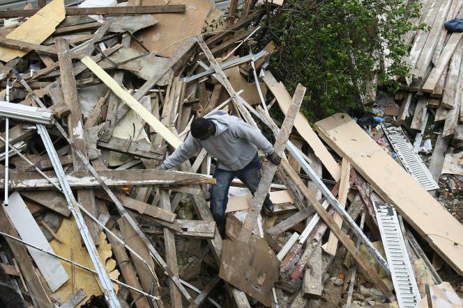 Un salarié sans-papiers en grève sur un chantier de démolition ramasse du bois pour faire un feu, à Paris, le 18 avril 2008.
