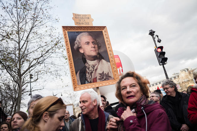 Troisieme journee de mobilisation contre la reforme des retraites. Un homme tient un pancarte represantant un tableau d Emmanuel Macron en monarque et lisant