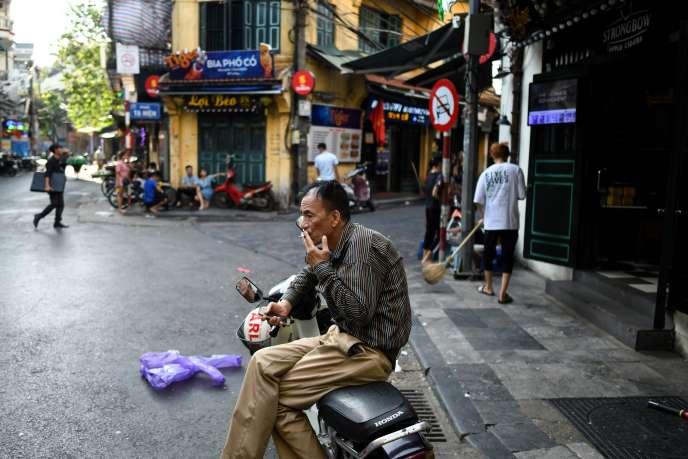 Un homme fume une cigarette dans une rue de Hanoï, au Vietnam, le 3 septembre.