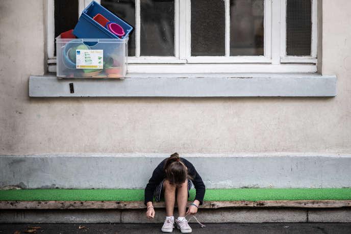 Une élève lace ses chausures dans une cour d'école à Paris, le 2 septembre.