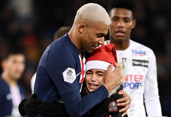 Kylian Mbappé prend dans ses bras un jeune fan qui a fait irruption sur la pelouse pour lui demander un autographe, le 21 décembre au Parc des Princes.
