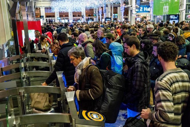 Départs en vacances le 20 décembre à gare de Lyon : les passagers passent portique de sécurité avec leur billet de train pour accéder aux quais.